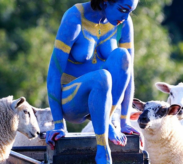 woman painted blue as Kali, surrounded by sheep at trough