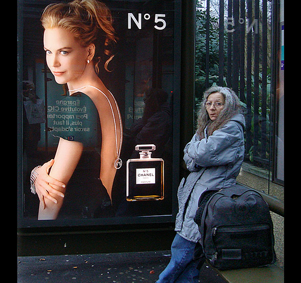 Photo of a grey-haired woman in a bus shelter standing next to a poster of Nicole Kidman for Chanel