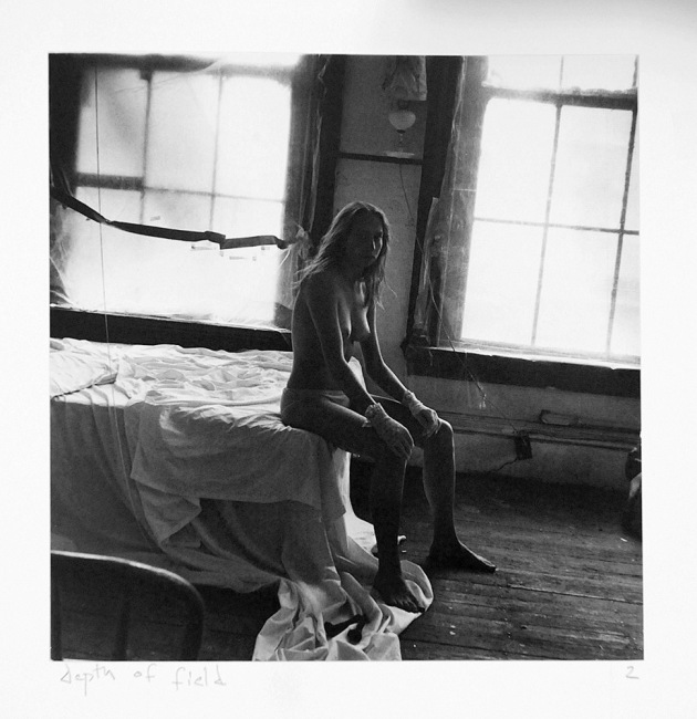 B&W wide-framed self-portrait of Vaneeesa Blaylock sitting semi-naked on the edge of a bed in an old house in The New Territories, Hong Kong