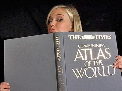 Caitlin Upton peering over the top of The Times Atlas of theWorld
