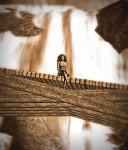The tiny figure of Vaneeesa Blaylock sits on a wooden bridge with an enormous waterfall at her back.