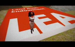 """Vaneeesa Blaylock stands on a giant red square with the writing """"Land Rush Endowment LEA"""" on it."""