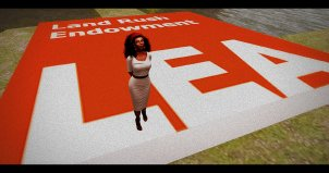 "Vaneeesa Blaylock stands on a giant red square with the writing ""Land Rush Endowment LEA"" on it."