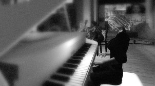 B&W Photo of Pianist Pixelated Gina performing on a white, grand piano, at Gallery Xue / NYC