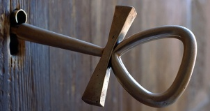 Photograph of a ankh shaped key in keyhole in a rustic wooden door