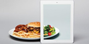 Image of greasy hamburger plate being transformed into a healthy salad by an iPad augmented reality display